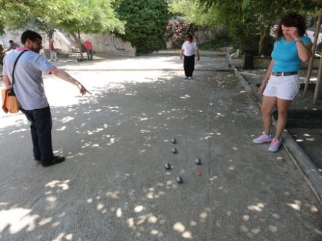 A spectator measures the boules